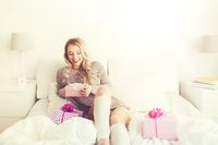 happy young woman with gift boxes in bed at home