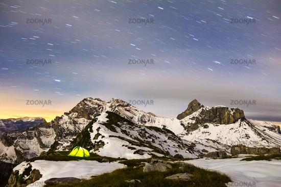 Tent glows under a starry night sky in snowy alpine mountains. Alps, Switzerland.