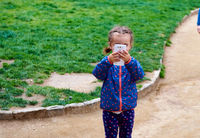Little girl making video or photo with mobile phone outdoors