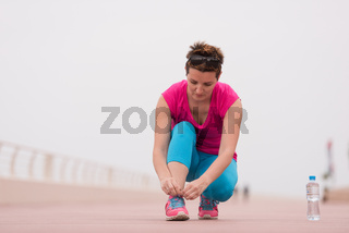 Young woman tying shoelaces on sneakers