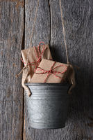 Closeup of a metal bucket hanging on a rustic wood wall with two Christmas presents inside.