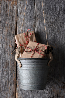 Presents in a bucket hanging on a rustic wood wall