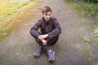 Portrait of a young man who is sitting on a way