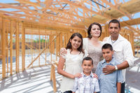 Young Hispanic Family On Site Inside New Home Construction Framing.
