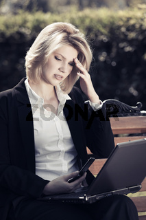 Young business woman with laptop sitting on a bench