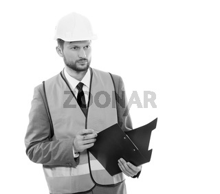 Male architect in a safety west and a hardhat writing on his cli