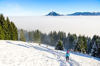 Sport, fitness inspiration and motivation. Young happy woman cross country running in mountains landscape on snow. Bavaria, Germany.