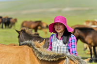 Young Mongolian woman with fashionable hat among horses, Mongolia