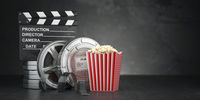 Cinema movie concept  background. Film reel and tape, popcorn and clapperboard on black grunge background