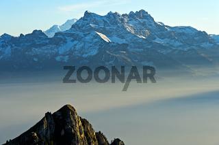 Bliick über den Herbstnebel im Rhone-Tal auf die Gipfel der Dents du Midi, Waadt, Schweiz