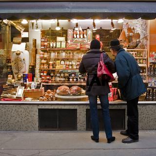 Ehepaar vor einem Delikatessengeschäft in Wien / couple before a delicatessen shop in Vienna