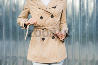 Close-up of woman ties a belt on a coat outdoors