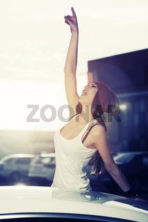 Happy fashion woman in tank top shouting beside a her car