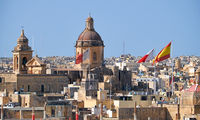 The view of St Lawrence church surrounded by flags raised about the holiday, Malta