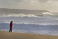 Junge Frau am Strand von Nazare bei grossen Wellen, Portugal, Europa