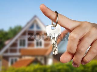 Hand mit Schlüssel vor einem Haus