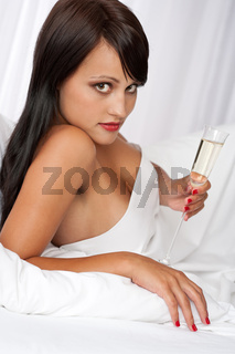 Portrait of naked woman with glass of champagne