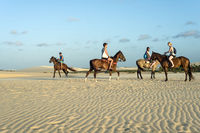 Tourists ride on horseback at Sunset Dune about an hour before sunset