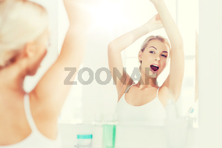 woman yawning in front of mirror at bathroom