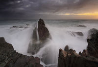 Stormy sunrise and waves crash over sea stacks
