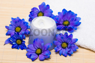 spa essentials, cream and towel with blue flowers