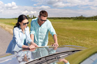 happy man and woman with road map on car hood