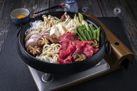 Traditional Sukiyaki pot with Kobe Beef and Vegetable as close-up on slate