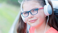 Cute girl listening to music with headphones outdoor in front of the car