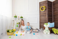 Delighted mother and her little child enjoying the Easter egg hunt at home