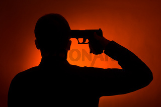 silhouette of the man pointing gun to his head