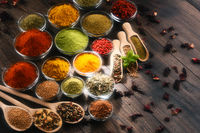 Variety of spices and herbs on kitchen table.