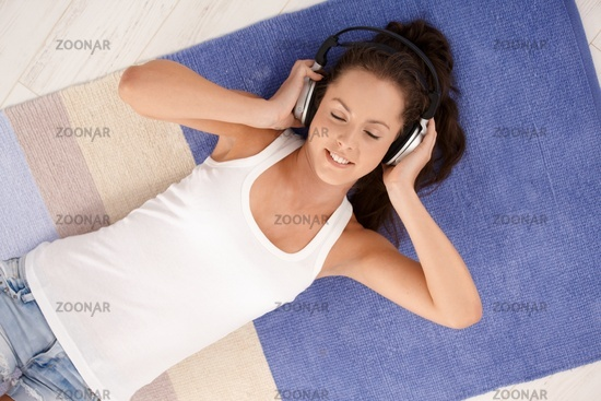 Attractive female laying on floor enjoying music