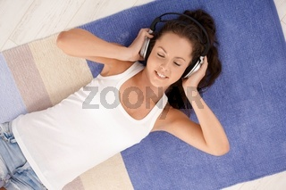 Attractive female laying on floor enjoying music