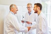 Ältere Arzt und Assistenzärzte schütteln Hände