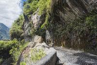 Cascades route, Banos - Puyo, Ecuador - December 8, 2017: Tourists ride bicycles along the Waterfalls Road over the precipice of the canyon
