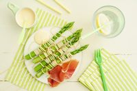 Skewers of steamed asparagus wrapped with spaghetti with hollandaise sauce and ham