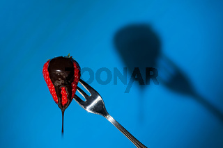Close up of a strawberry and its shadow on background