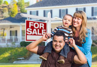 Young Family in Front of For Sale Sign and House