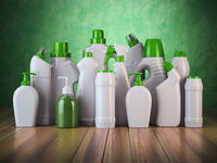 Natural green detergent bottles or containers. Cleaning supplies on green background