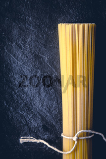 Raw spaghetti on the black stone background  vertical
