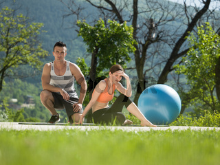 woman with personal trainer doing morning yoga exercises