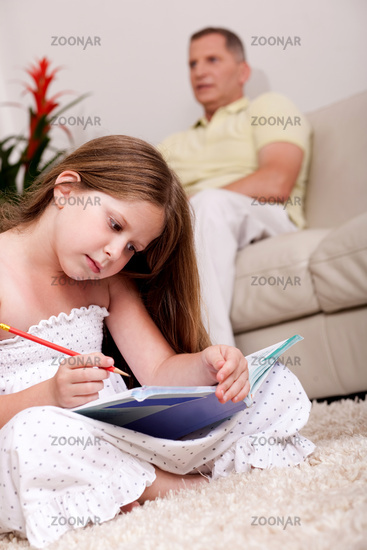 An attractive cute girl doing her homework with her father in the background