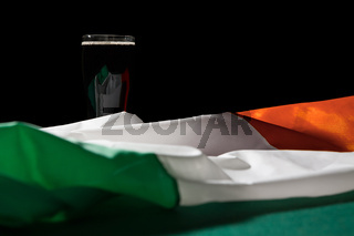 St Patrick day with a pint of black beer and irish flag over a green table