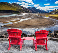 Two red chaise lounges for tourists