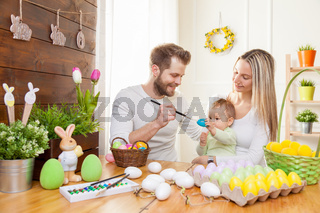 Easter concept. Happy and loving mother and father preparing home decoration with their child for Easter holidays