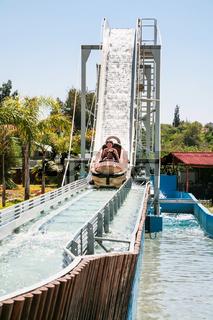children in boat on water slide attraction