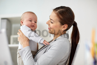 happy businesswoman with baby at office