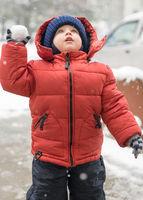 Infant boy looks upwards while snowing