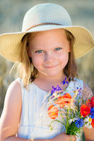 Little cheerful girl in a straw hat with wild flowers red poppy bouquet in the summer meadow - coquettish, mischievous face