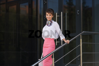 Young fashion business woman in white blouse and pencil skirt at office building